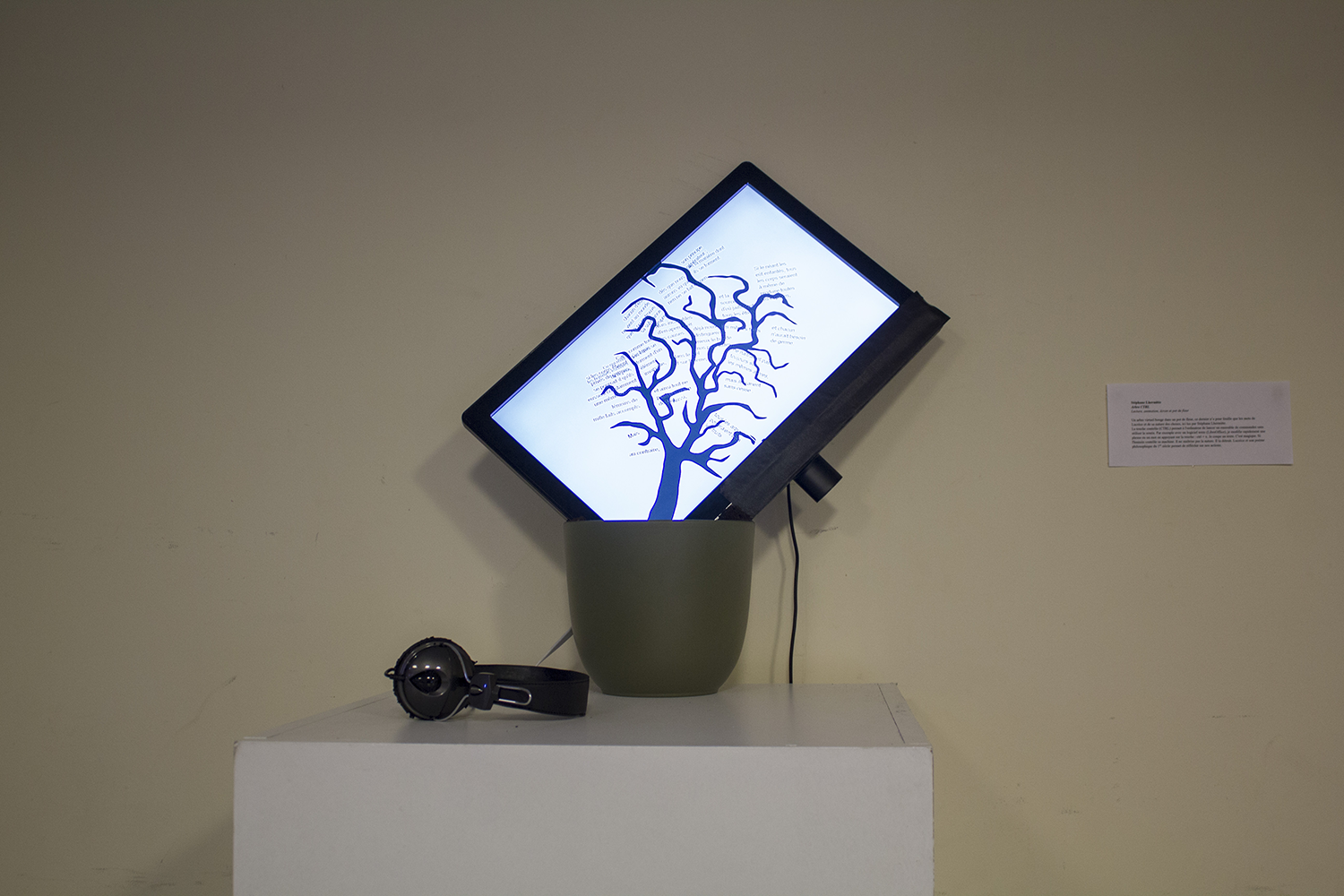 A screen is inside a flower pot and show a tree of words